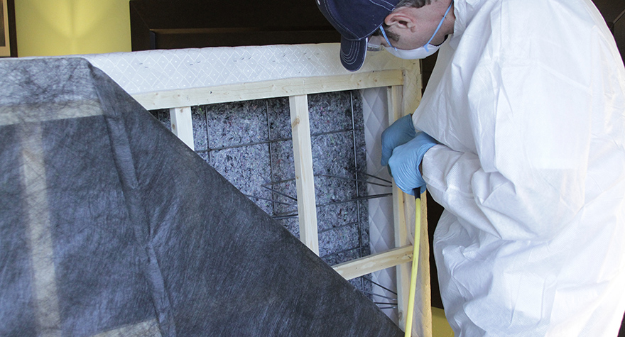 Pest professional applying boxspring treatment